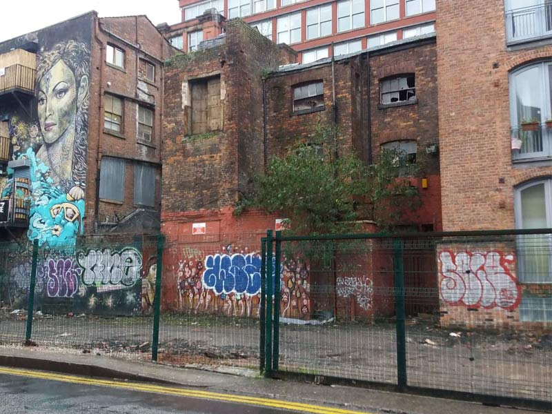 A derelict building with smashed windows and graffiti in Manchester