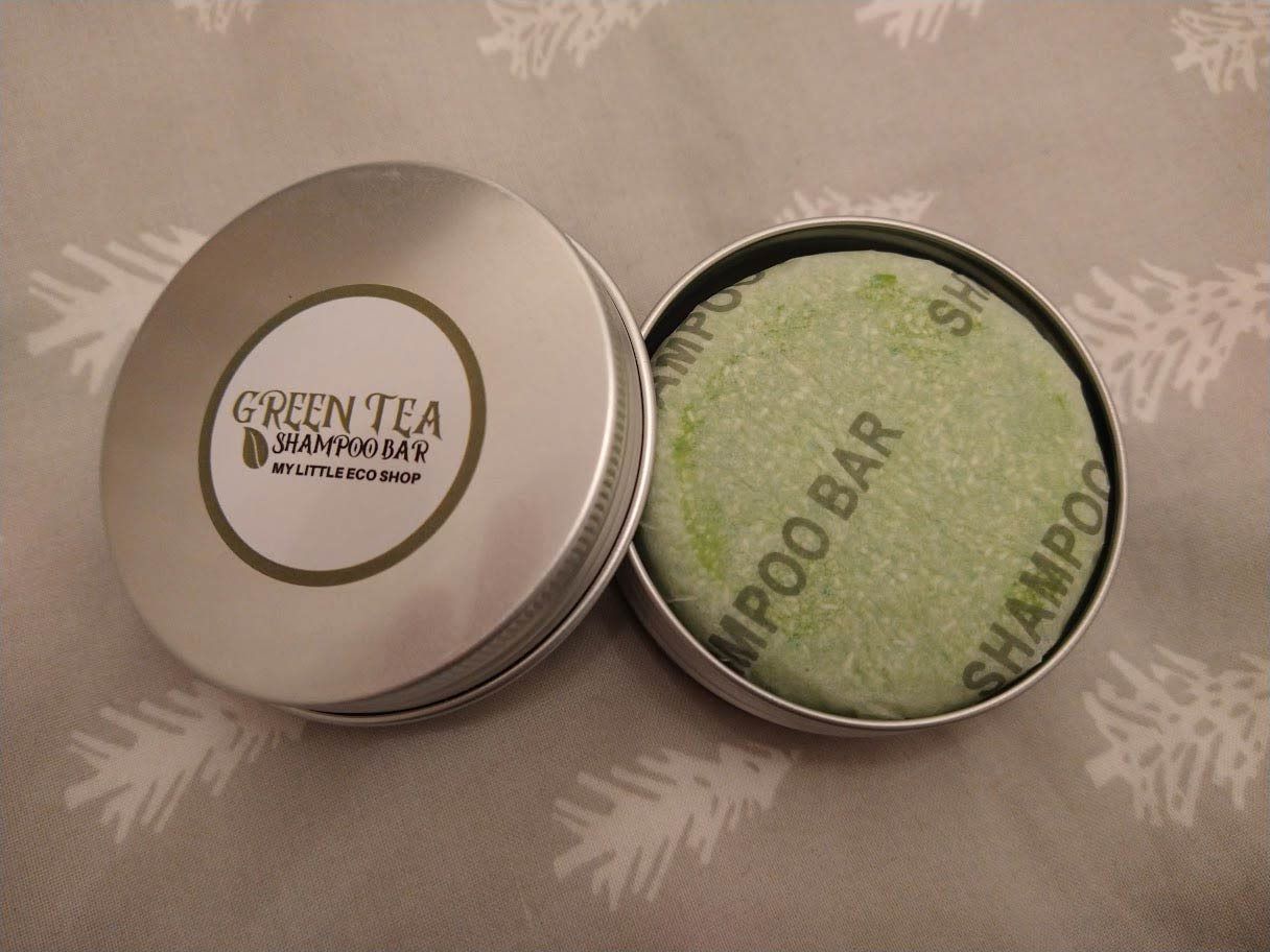The My Little Eco Shop's green tea shampoo bar wrapped in paper and in a tin.