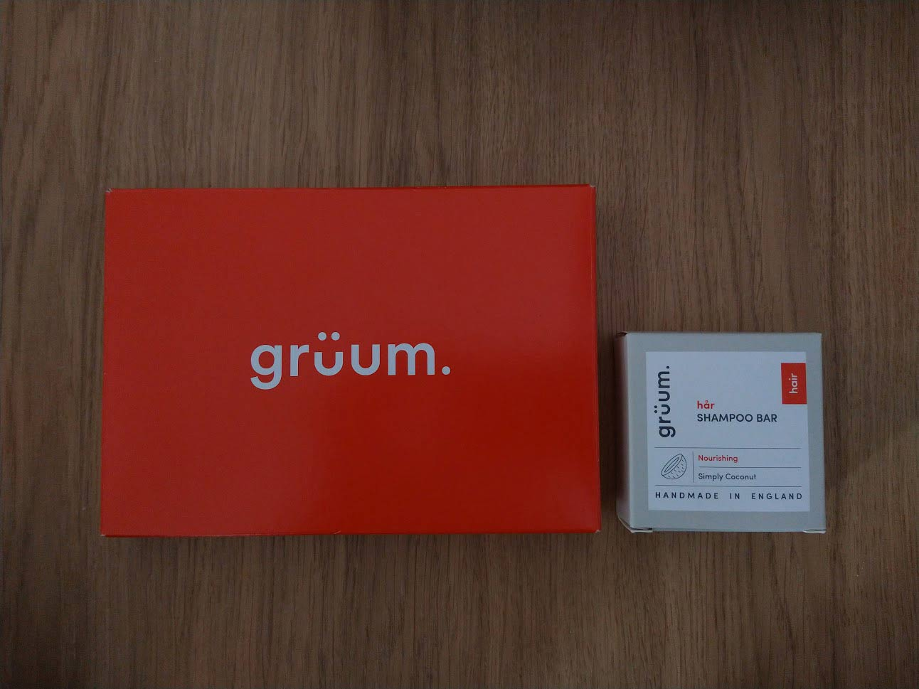 Grüum packaging: a red cardboard box beside the smaller square box that contains the shampoo bar.