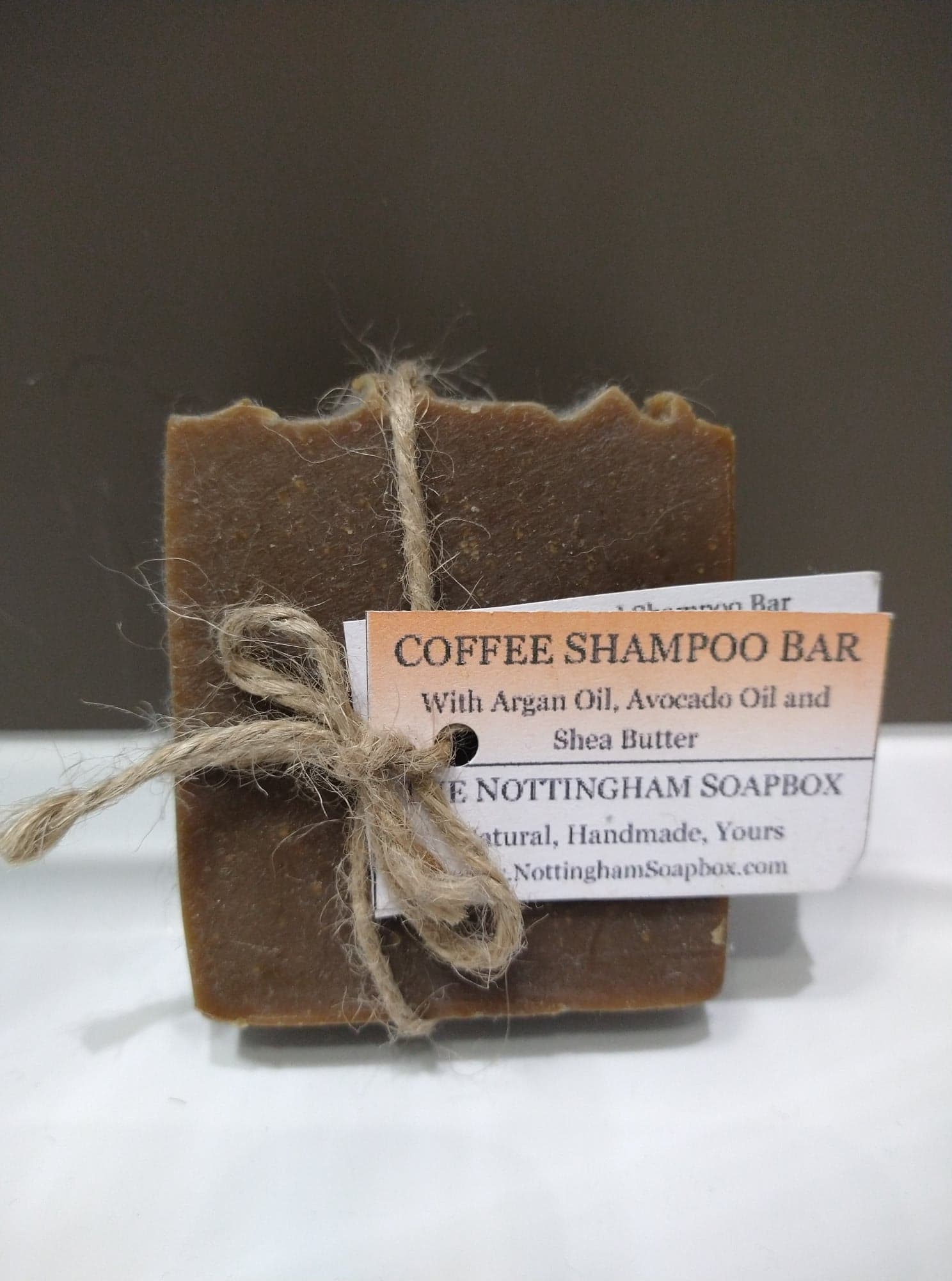 A brown block of Nottingham Soapbox coffee shampoo bar, with a string bow and label.