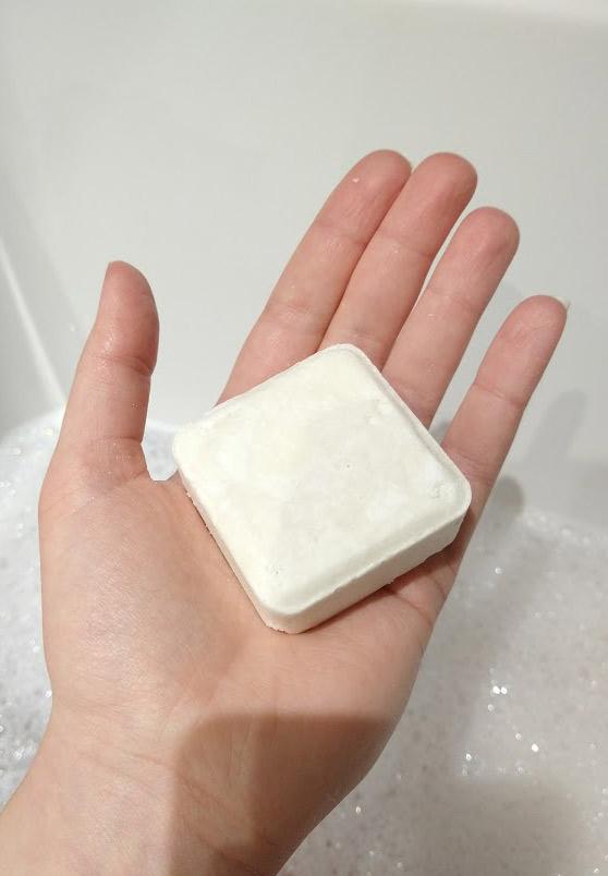 The Zero Waste Path square white shampoo bar in my hand.