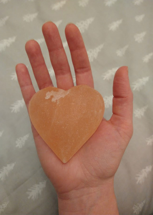 A heart-shaped bar of Himalayan salt in the palm of my hand for size reference.