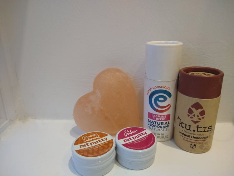 A selection of five natural deodorants - a heart-shaped Himalayan salt bar, Earth Conscious and 'ku.tis sticks, and two small tins of Pit Putty.